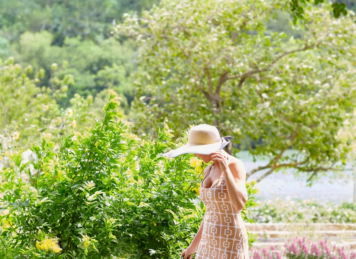 Woman in a long dress and sun hat strolls through the luscious Lake Austin gardens