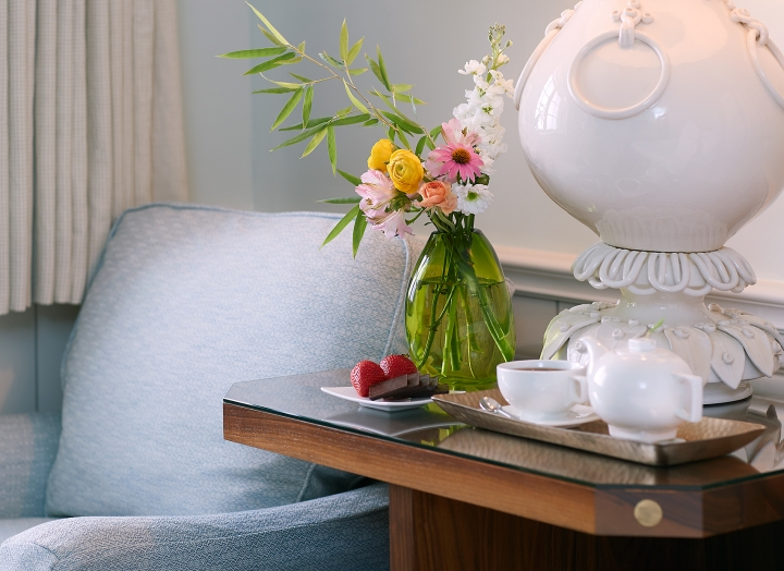 Bedside table with fresh flowers and a lounge chair in the Luxury LakeView room