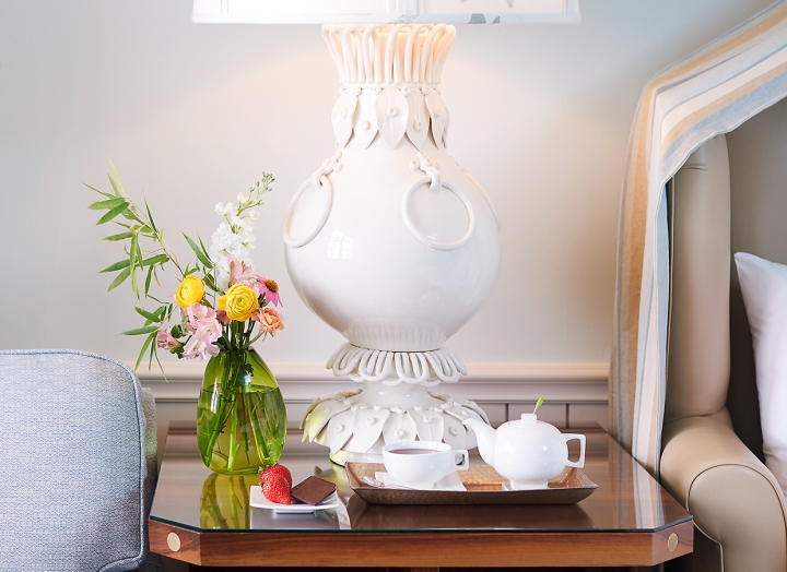 Bedside table with fresh flowers and large white lamp in the Luxury LakeView room