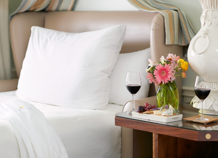 Bedside table with fresh flowers and two glasses of red wine in the Luxury LakeView room