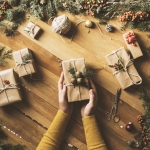 Christmas, New Year concept table top flat lay on wooden background. Woman wearing yellow mustard cardigan wrapping gifts. Wrapping paper, jute string, gift box, Christmas ornament, pine cones and firethorn branches on wooden background.
