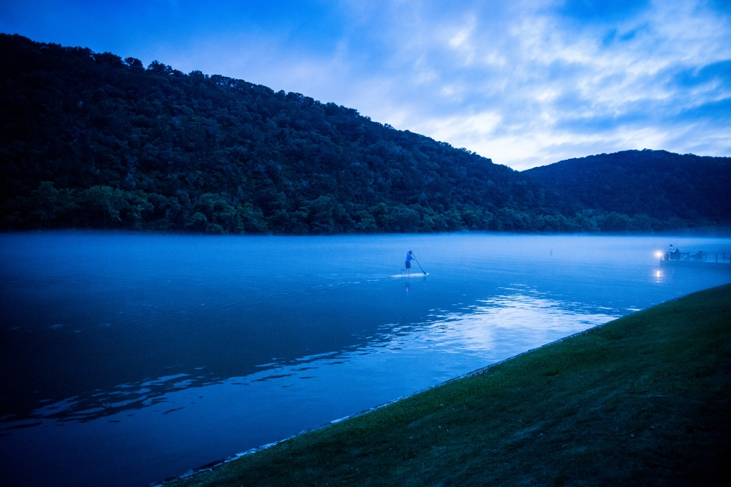 A man on a stand up paddleboard on Lake Austin at dusk