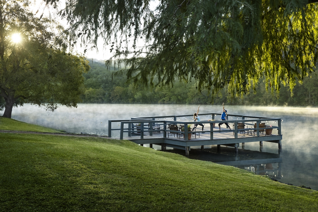 Woman and instructor doing yoga on dock in the early morning with fog coming off the lake at Lake Austin Spa Resort