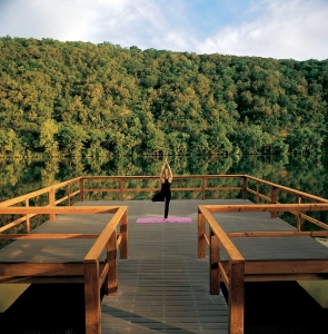 A woman does yoga as the sunrises on a dock over Lake Austin.