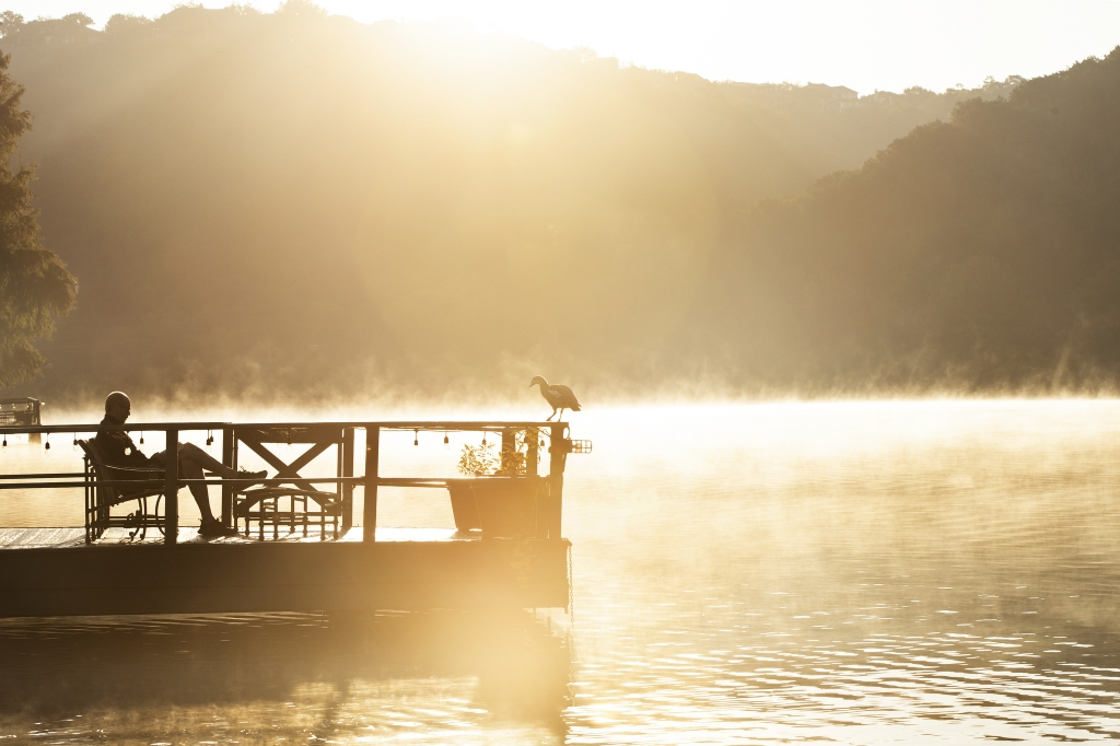 Silhouetted man reading on dock in the early morning with fog coming off the lake at Lake Austin Spa Resort
