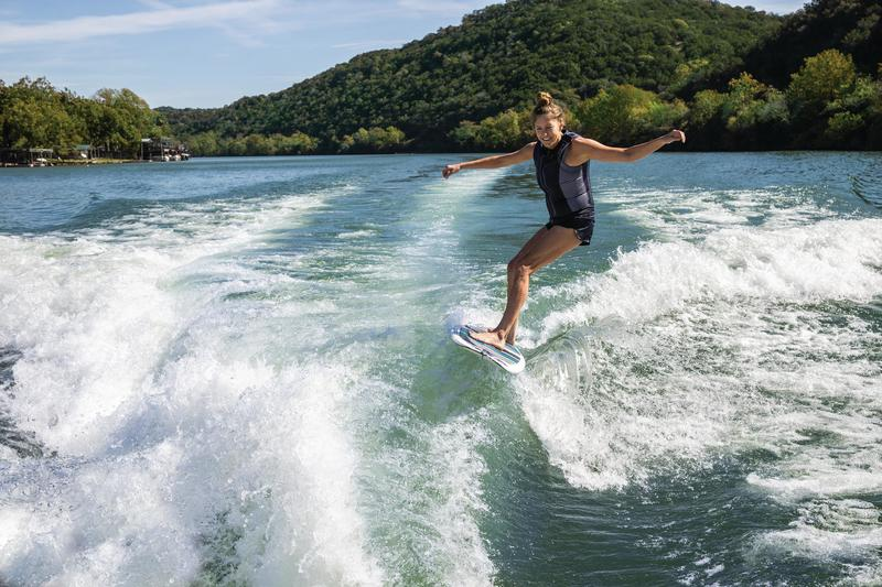 woman wakesurfing behind a boat