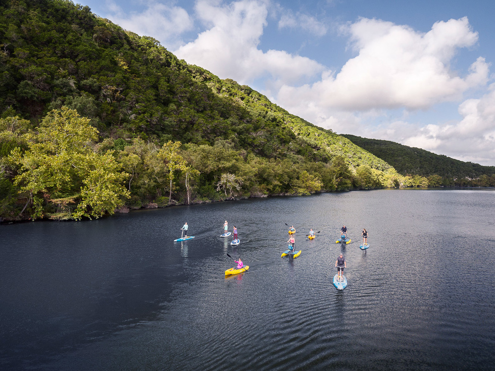 group of people on various kayaks and paddle boards on Lake Austin