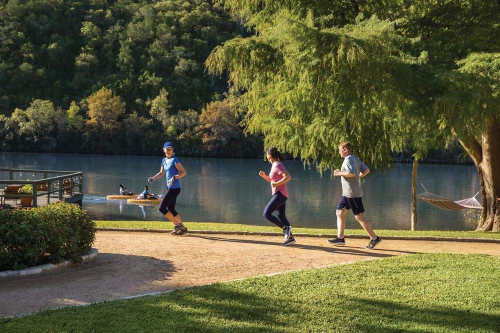 Three people jogging along the lake at Lake Austin Spa Resort