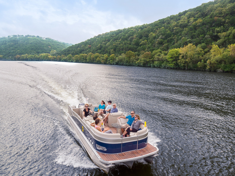 drone shot of pontoon boat cruising on Lake Austin