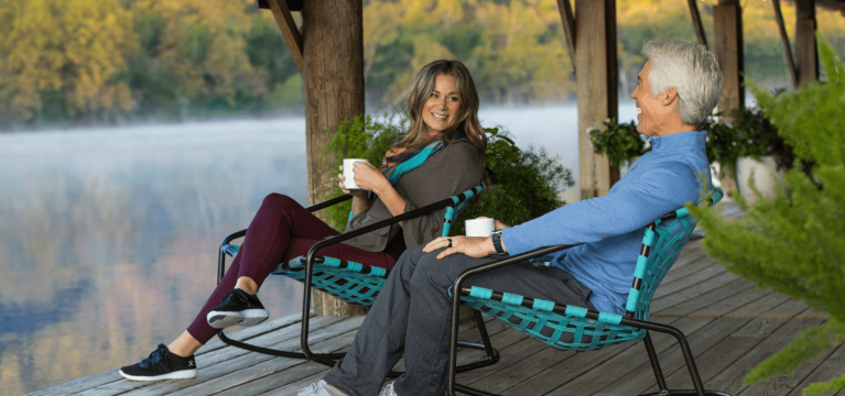A couple drinking coffee on sitting on outdoor rocking chairs while overlooking the lake