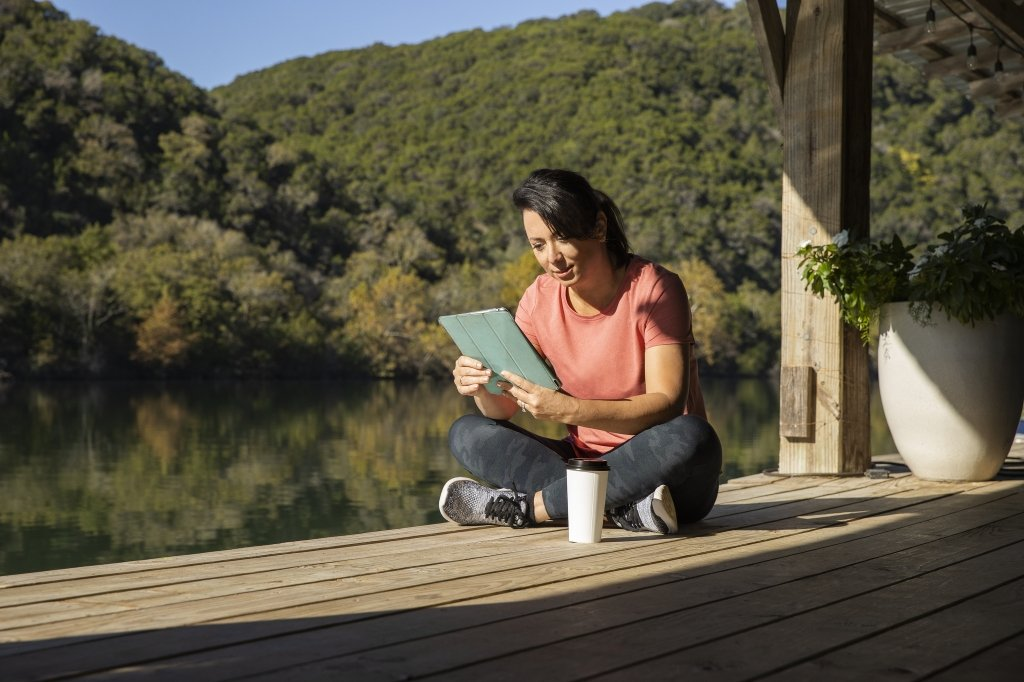 woman reading a tablet on the boat dock at Lake Austin Spa Resort